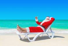 Santa Claus sfoglia sul gesturing sul sunlounger alla spiaggia tropicale fotografie stock libere da diritti