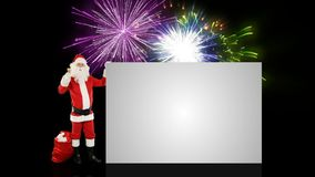 Santa Claus shaking bell presenting a white sheet, against holiday fireworks stock video footage