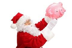 Santa claus shaking a piggybank. Isolated on white background Stock Image