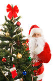 Santa Claus Shhhhhh. Santa Claus peeking around the Christmas tree gesturing for you to be quiet Royalty Free Stock Images
