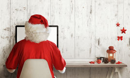 Santa Claus shopping on computer. Christmas sale time. Free space for text Royalty Free Stock Images
