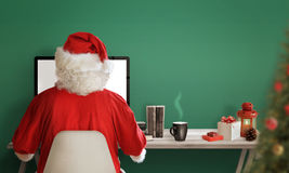 Santa Claus shopping online during the Christmas sale. Christmas gifts, tree, tea, books and decorations on table. Free space for text. Green wall in royalty free stock images