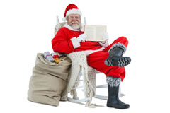 Santa claus showing bible with sack of christmas present beside him Stock Photography