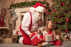 Santa Claus showing Christmas presents. To little kid Stock Images