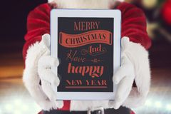 Santa claus showing digital tablet with christmas greeting Royalty Free Stock Photo