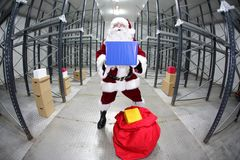 Santa Claus showing gift  in empty storehouse Stock Photo