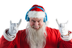 Santa claus showing hand yo sign while listening to music on headphones Stock Image