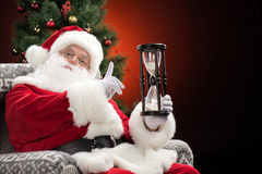 Santa Claus showing hourglass Royalty Free Stock Photos