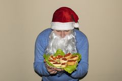 Santa Claus shows a lot of sandwiches with red caviar. royalty free stock photo