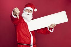 Santa Claus shows thumbs down, advertisement in hand Stock Photography