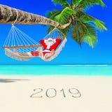 Santa Claus si rilassa in amaca sotto la palma alla spiaggia tropicale dell'isola con il titolo scritto a mano 2019 buoni anni fotografia stock