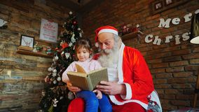 Santa Claus si siede sulla poltrona e legge il libro con le fiabe per la bambina entusiasta nella stanza festiva decorata stock footage