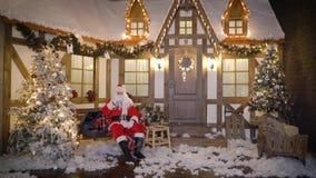 Santa Claus si siede vicino alla casa fra gli alberi di Natale, bevande munge, mangia i biscotti, ascolta canzoni di natale su vi video d archivio