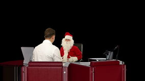 Santa Claus is sick, Doctor measuring blood pressure, against black, stock footage Royalty Free Stock Images