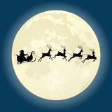 Santa Claus silhouette with deers in front of moon Royalty Free Stock Photo