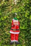 Santa Claus simpática está pendurando de uma corda branca Fotografia de Stock Royalty Free