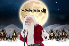 Santa claus singing christmas song in microphone. During christmas time Royalty Free Stock Photos