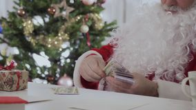 Santa Claus sit on the table and counting money. Santa Claus with a white long beard sit on the table and counting money near Christmas tree stock footage