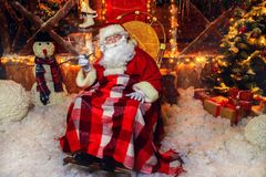 Sits in armchair. Santa Claus sits in an armchair and smokes a pipe. House of Santa Claus. Christmas decoration royalty free stock photos
