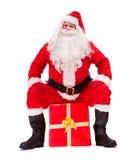 Santa Claus sits on a Christmas gift box Stock Image