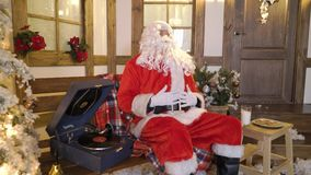 Santa Claus sits near the house between christmas trees, drinks milk, eats cookies, listens christmas songs on vinyl by. Gramophone, relaxes, enjoys, miss alone stock video