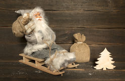 Santa Claus sits on a wooden sleigh with a bag of gifts behind h. Santa Claus in grey costume sits on a wooden sleigh with a bag of gifts behind her back Royalty Free Stock Images