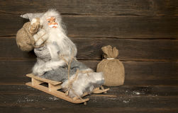 Santa Claus sits on a wooden sleigh with a bag of gifts behind h. Er back and a sack of gifts stands next to the sled. Christmas concept Royalty Free Stock Photo