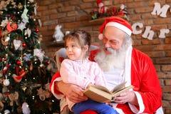 Santa Claus sitter på fåtöljen och läser boken med sagor fo Fotografering för Bildbyråer