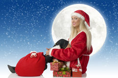 Santa claus sitting. Blond santa claus with gift and black boot sitting and smiling Stock Photos