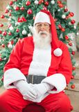 Santa Claus Sitting Against Christmas Tree Fotografia de Stock