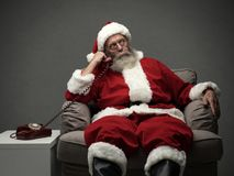 Santa Claus on the phone. Santa Claus sitting on the armchair and having a phone call, he is holding a receiver and listening royalty free stock image
