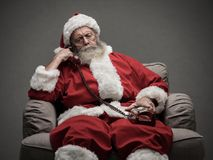 Santa Claus on the phone. Santa Claus sitting on the armchair and having a phone call, he is holding a receiver and listening stock photos