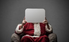 Santa Claus holding a sign. Santa Claus sitting on an armchair and holding a blank sign, Christmas wishes and advertising concept Royalty Free Stock Photography
