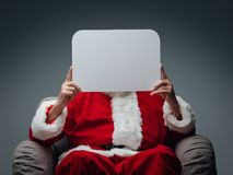 Santa Claus holding a sign. Santa Claus sitting on an armchair and holding a blank sign, Christmas wishes and advertising concept Royalty Free Stock Images