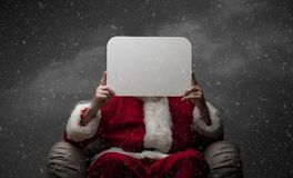 Santa Claus holding a sign. Santa Claus sitting on an armchair and holding a blank sign, Christmas wishes and advertising concept Stock Images