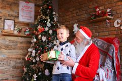 Curious male child receives gift from Santa Claus in decorated f Royalty Free Stock Images