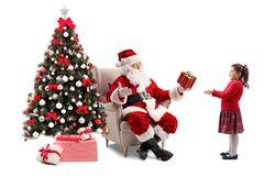 Santa Claus sitting in an armchair next to a Christmas tree and royalty free stock photo