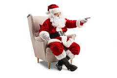 Santa Claus sitting in an armchair and pointing stock photo