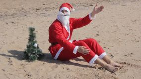 Santa claus is sitting on the beach  welcomes celebration christmas new year. Santa claus is sitting on the beach welcomes celebration christmas new year relax stock video footage