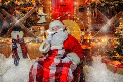 Smoking a pipe santa. Santa Claus is sitting in a chair, covered in a blanket and smoking a pipe. House of Santa Claus. Christmas decoration royalty free stock photography