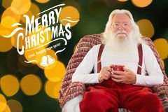 Santa claus sitting on chair and holding coffee mug Royalty Free Stock Photography