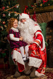 Santa Claus sitting in a chair with a little girl. Fireplace and Christmas tree in the background Royalty Free Stock Photos