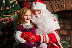 Santa Claus sitting in a chair with a little girl. Fireplace and Christmas tree in the background Stock Images