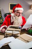 Santa Claus reading a letter. Santa Claus sitting on chair and reading a letter at home Stock Images