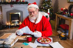 Santa Claus reading a letter. Santa Claus sitting on chair and reading a letter at home Royalty Free Stock Images