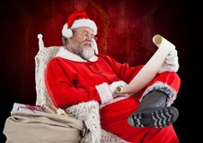 Santa claus sitting on a chair and reading wish list. Against red background Royalty Free Stock Images