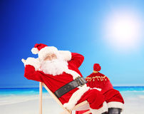 Santa Claus sitting on a chair and relaxing, on a beach Stock Photography