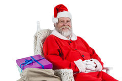 Santa claus sitting on chair with sack of christmas present beside him Stock Photo