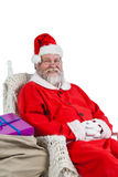 Santa claus sitting on chair with sack of christmas present beside him Stock Photos
