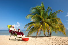 Santa Claus sitting in deck chair on beach Royalty Free Stock Image